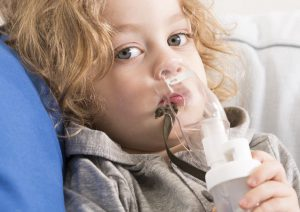 Close-up of little boy suffering from asthma taking inhalation